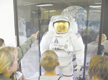 "Children in the ""Federation of Galaxy Explorers, Moon Base One Camp,"" at Jack Swigert Aerospace Academy, get an up-close look at an astronaut's suit. They learned that the suit has sensors on the fingertips and weighs 630 pounds on Earth, but only weighs 65 pounds on the moon. The suit is on permanent display at Swigert school and was a gift from The Space Foundation in Colorado Springs, located on the same campus with Swigert school. (U.S. Air Force photo/Monica Mendoza)"