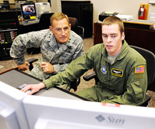 Maj. Gen. Michael Basla, Air Force Space Command vice commander, listens as Airman 1st Class Ryan Coffey, 2nd Space Operations Squadron, explains one of the unit's systems during the General's visit to Schriever Sept. 2. The General's tour consisted of a wing mission briefing, tours of the space operations squadrons, and a lunch.  (U.S. Air Force Photo/Dennis Rogers)