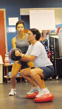 Master Sgt. Amber Mitchell, 1st Space Operations Squadron, trains at the Schriever fitness center as Patti Eafrati, Schriever Fitness Center Personal Trainer, spots. Sergeant Mitchell dropped 15 pounds, cut five inches off her waist and scored a 92 on the Air Force Fitness Assessment following five weeks of personal training with Ms. Eafrati. (U.S. Air Force photo\Scott Prater)