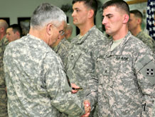 U.S. Army Chief of Staff Gen. George W. Casey, Jr. presents a coin to Sgt. Clyde Skinner III, a forward observer assigned to the Fires Section, Company A, Division Special Troops Battalion, 4th Infantry Division, during a ceremony at Contingency Operating Base Speicher, Iraq, Dec. 24.