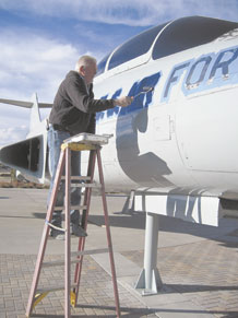 "An employee from Enviro-Tech, a Georgia-based company that specializes in restoring, treating and painting static display aircraft, paints the U.S. Air Force name across the forward fuselage of the F-101 ""Voodoo"" aircraft Dec. 15 on Peterson Air Force Base. The work is part of a $76,000 restoration project of several aircraft at the Peterson Air and Space Museum funded North American Aerospace Defense Command and U.S. Northern Command. (U.S. Air Force photo/Jeff Nash)"