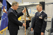 """Lt. Col. Aaron Bass, 21st Operations Group standardization and evaluation chief, presents Master Sgt. Micheal Meyer, 21st OG noncommissioned officer in charge of standardization, with the """"Old Man of Space Staff"""" Dec. 8, at the Peterson Air and Space Museum on Peterson Air Force Base during Sergeant Meyer's retirement ceremony. Sergeant Meyer, who officially retires April 1, 2011, is the longest serving space operator in Air Force Space Command. He joined the Air Force in 1986 when space operator was a new career field for enlisted troops. (U.S. Air Force photo/Dennis Howk)"""
