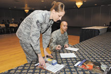 Staff Sgt. Jessica Thomas (front), Air Force Office of Special Investigations, collects her Air Force Assistance Fund sign-up slips and poster from Senior Master Sgt. John Bentivegna, 76th Space Control Squadron superintendent and a Peterson 2011 AFAF installation project officer. Unit reps received breakfast and training March 29 at The Club on how to effectively manage and distribute AFAF information to unit personnel. The campaign is underway now to May 6. (U.S. Air Force photo/Craig Denton)