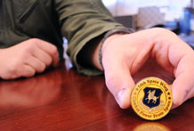 An Air Force service member presents a 50th Space Wing coin. Challenge coins have been an American military tradition for nearly a century. They represent exemplary service, shared sacrifice and unit espirit.  (U.S. Air Force photo/ 2nd Lt. Marie Denson)