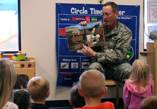 (U.S. Air Force photo/Staff Sgt. Patrice Clarke) Col. Brian Barthel, 50th Mission Support Group commander, reads to children at the Schriever Child Development Center recently. The CDC here recently received a facelift to include new paint and furniture.