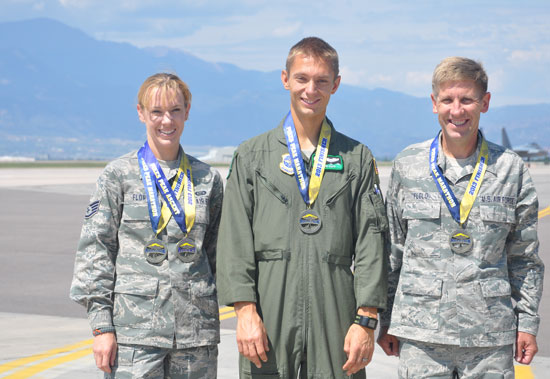 (U.S. Air Force photo/Ann Skarban)  With Pikes Peak visible from the Peterson Air Force Base flightline, 302nd Airlift Wing members Staff Sgt. Denise Flory, Capt. Steven Paap and Lt. Col. Alan Flolo, display their marathon medals. Flory, 302nd Airlift Wing historian, Paap, a C-130 pilot with the 52nd Airlift Squadron and Flolo, commander of the 302nd Force Support Squadron were all finishers of the Aug. 19 Pikes Peak Marathon, which is rated the second most  difficult marathon in the world.