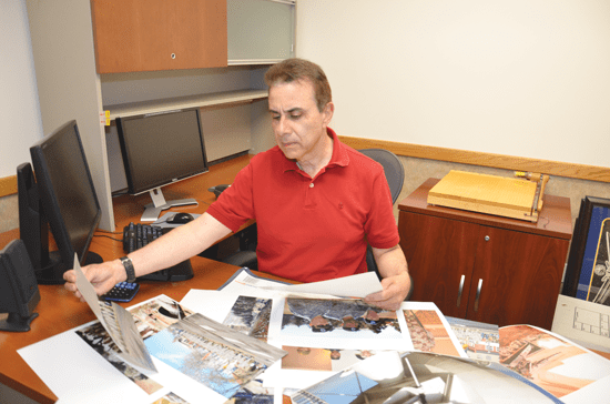 (U.S. Army photo/Sharon Hartman)  Don Montoya looks over prints of 1st Space Brigade subject matter to determine the best final shot for a display wall.