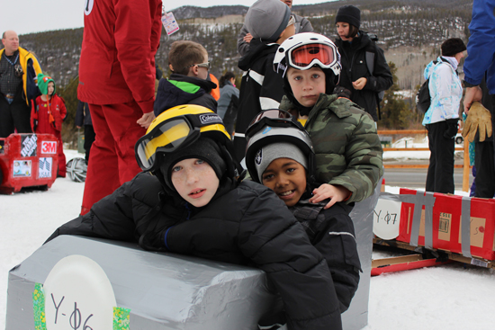 (U.S. Air Force photo/1st Lt. Stacy Glaus). Maj. Frankie Robinson and Maj. Charles Michaels' children prepare to brave Discovery slope at Keystone Resort during SnoFest's cardboard derby Jan. 26, 2013.