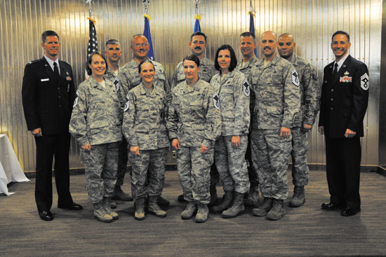 (U.S. Air Force photo/Robb Lingley) PETERSON AIR FORCE BASE, Colo. — Col. Richard Burchfield (left), 21st Space Wing IMA to the commander, and Chief Master Sgt. Richard Redman (right), 21st SW command chief, present stripes to the Team Pete's newest crop of senior master sergeants March 21 at The Club. Eighteen master sergeants from Team Pete were selected for promotion to E-8.