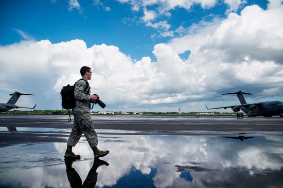 """U.S. Air Force photo/ Senior Airman George Goslin Senior Airman Dennis Sloan, 628th Air Base Wing Public Affairs photojournalist, walks on the Joint Base Charleston flightline in search of a photo May 5, 2013. A victim of sexual assault, Sloan says his passion for photography """"keeps (him) breathing"""" and offers solace from his otherwise painful memories."""