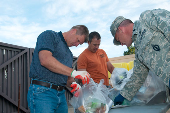 "Air Force photo/Senior Airman Naomi Griego Lt. Col. Bart Hughes (right), 50th Space Wing chief Plans and Programs, David Duhe (left), 50 SW XP signature manager, and Frank Vigil, 50th Space Wing information protection officer, sort through trash during the ""dumpster dive"" Sept. 4, 2014, at Schriever Air Force Base, Colo. The dumpster dive was a base initiative designed to thwart operational security violations and personally identifiable information from being carelessly discarded."