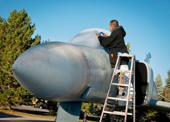 (U.S. Air Force photo/Staff Sgt. J. Aaron Breeden)  PETERSON AIR FORCE BASE, Colo. – Anthony Garcia, a painting contractor, masks the cockpit of an F-4 Phantom II aircraft with paper and tape in preparation for paint at the base museum Oct. 30. Garcia is part of a contracted crew hired to repaint and touch up 10 aircraft maintained by the museum to ensure these artifacts remain accurate representations of these once high-soaring crafts that now reside at Peterson AFB.