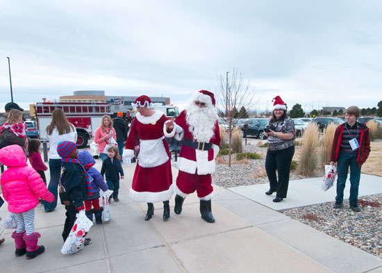 U.S. Air Force photo/Senior Airman Naomi Griego Mr. and Mrs. Claus greet children at the front door of the Children's Holiday Festival Saturday at Schriever Air Force Base, Colo. Nearly 1,700 people attended the 14th annual Schriever event.