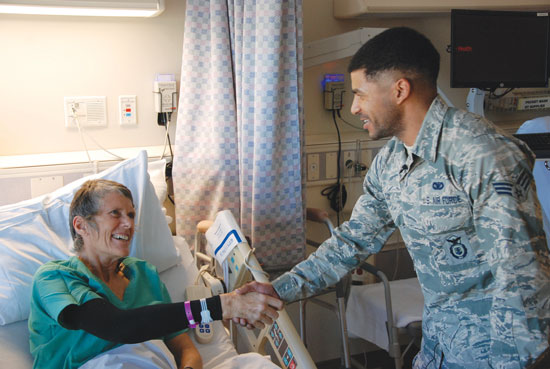 (U.S. Air Force photo by Dave Smith)  COLORADO SPRINGS, Colo. -- Ali Watts and Senior Airman Elliott Cox, 721st Security Forces Squadron, happily greet each other Jan. 15 at Memorial Hospital. On Jan. 2 Cox responded to Watts' cries for help after she broke her femur in a skiing accident at Monarch Mountain ski area. Because of his Air Force training, Cox was able to provide first aid, and comfort and stabilize Watts until medical help arrived. Watts had to be airlifted from the scene for medical treatment.