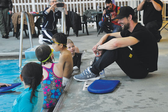 (U.S. Air Force photo by Robert Lingley)  PETERSON AIR FORCE BASE, Colo. – Michael Phelps, 22-time Olympic medalist in swimming, visits with Team Pete im8 swim program participants at the pool March 2, 2015. Phelps came to see the program in action with the swim instructors teaching the im safe module to 14 kids, and taught the kids a few tricks of his own to master their swimming techniques.