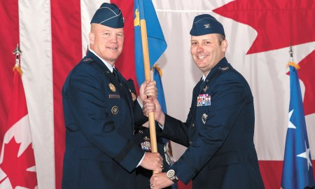 """(U.S. Air Force photo by Craig Denton) PETERSON AIR FORCE BASE, Colorado -- Lt. Gen. John W. """"Jay"""" Raymond, commander, 14th Air Force (Air Forces Strategic) and Joint Functional Component Command for Space, passes the 21st Space Wing guidon to Col. Douglas A. Schiess, incoming 21st SW commander, during the wing change of command ceremony June 12 in hangar 140. Before taking command of the wing, Schiess was Director of Space Forces, U.S. Air Forces Central Command, U.S. Central Command."""