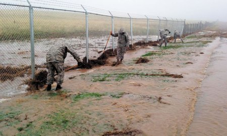 Photo courtesy of Tom Gary Members of the 50th Civil Engineer Squadron pull debris away from the perimeter fence during a rash of severe storms May 9, 2015 at Schriever Air Force Base, Colo. The group worked around-the-clock and had to weather rain, hail, lightning and a tornado warning in order to keep the fence intact.