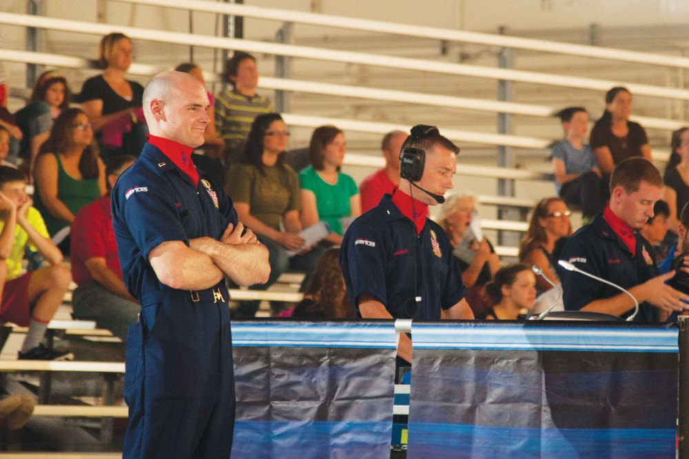 (U.S. Air Force Senior Airman Tiffany DeNault)  PETERSON AIR FORCE BASE, Colo. – 1st Lt. Ethan Frazier, 21st Force Support Squadron chief of military personnel and Tops in Blue technical director, smiles as he watches the Tops in Blue Performance at Hangar 140, July 1, 2015. Frazier's passion for entertainment production began six years before joining the Air Force, and he seized an opportunity to be a technical director for Tops in Blue, teaching other Airmen lighting, audio, video and staging techniques.
