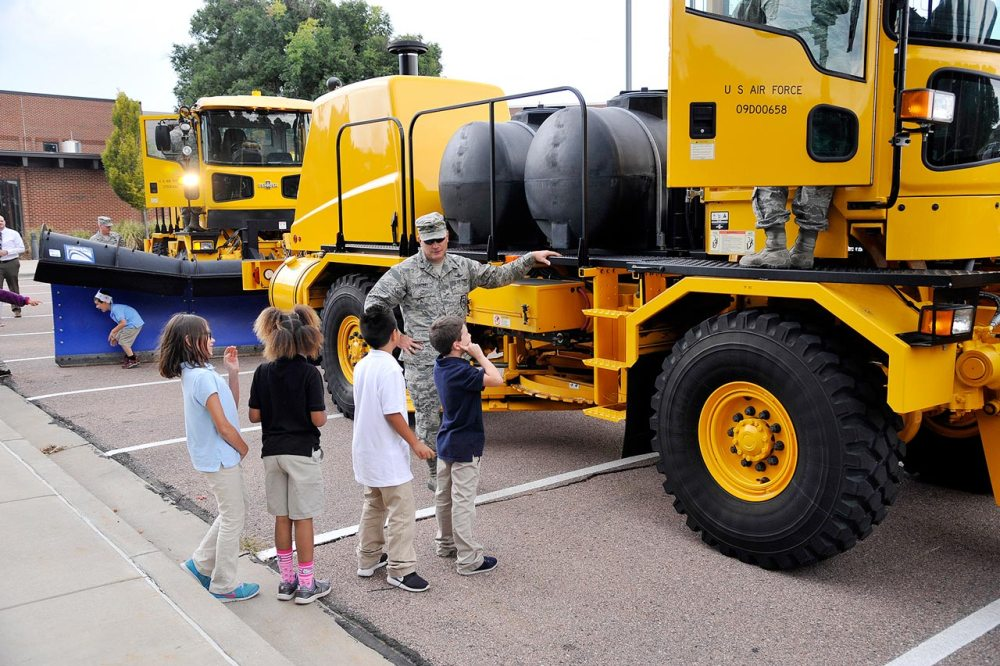 "U.S. Air Force photo by Robb Lingley PETERSON AIR FORCE BASE, Colo. — Col. Eric Dorminey, 21st Space Wing vice commander, visits with children at the R.P. Lee Youth Center during the annual ""Snow Parade"" down Peterson Boulevard on Sept. 29, 2015. The parade visited children at the Child Development Centers and youth center and let them explore the machinery. The annual parade is a way to show off the CES equipment and crews who work to make Peterson roadways safe and emphasize the need to keep roadways clear and accessible for emergency vehicles."