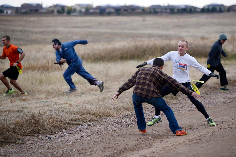 "U.S. Air Force photo/Christopher DeWitt Chris Babcock, 50th Space Communications Squadron, tries to avoid a zombie during the Zombie Run at Schriever Air Force Base, Colorado, Friday, Oct. 30, 2015. Babcock was the first survivor to reach the finish line following a ""horrifying, terrifying"" run."