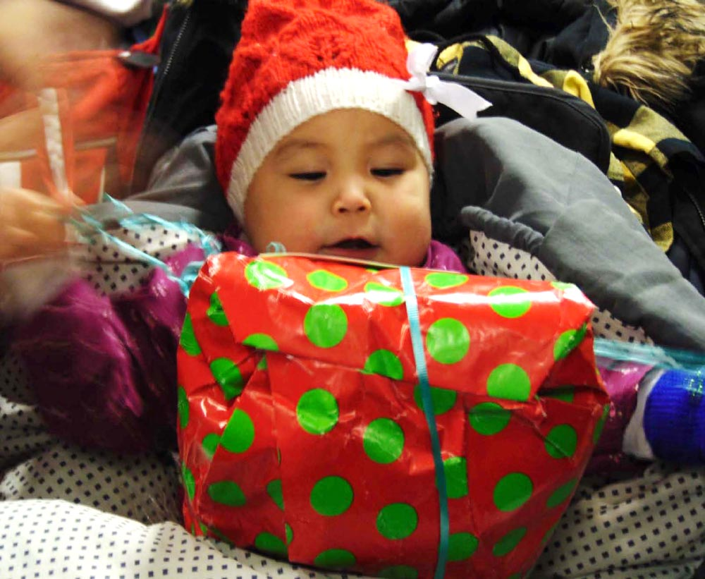 (U.S. Air Force photo by Staff Sgt. Victoria Camarillo) QAANAAQ, Greenland — A Qaanaaq child explores her Julemand gift Dec. 22, 2015. The gift-giving was part of Operation Julemand, an annual tradition by Thule Air Base personnel to donate toys and educational materials to Greenlandic children. The program has been going since 1959.