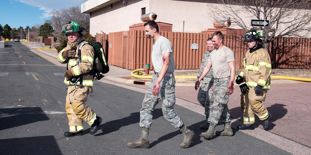 PETERSON AIR FORCE BASE, Colo. — Peterson firefighters evacuate role players while performing recovery operations following a simulated building explosion and resulting fire here during the 16-2 Condor Crest Exercise on Feb. 18, 2016. The exercise tested the 21st Space Wing and associate units' response to several incidents during the week-long exercise.