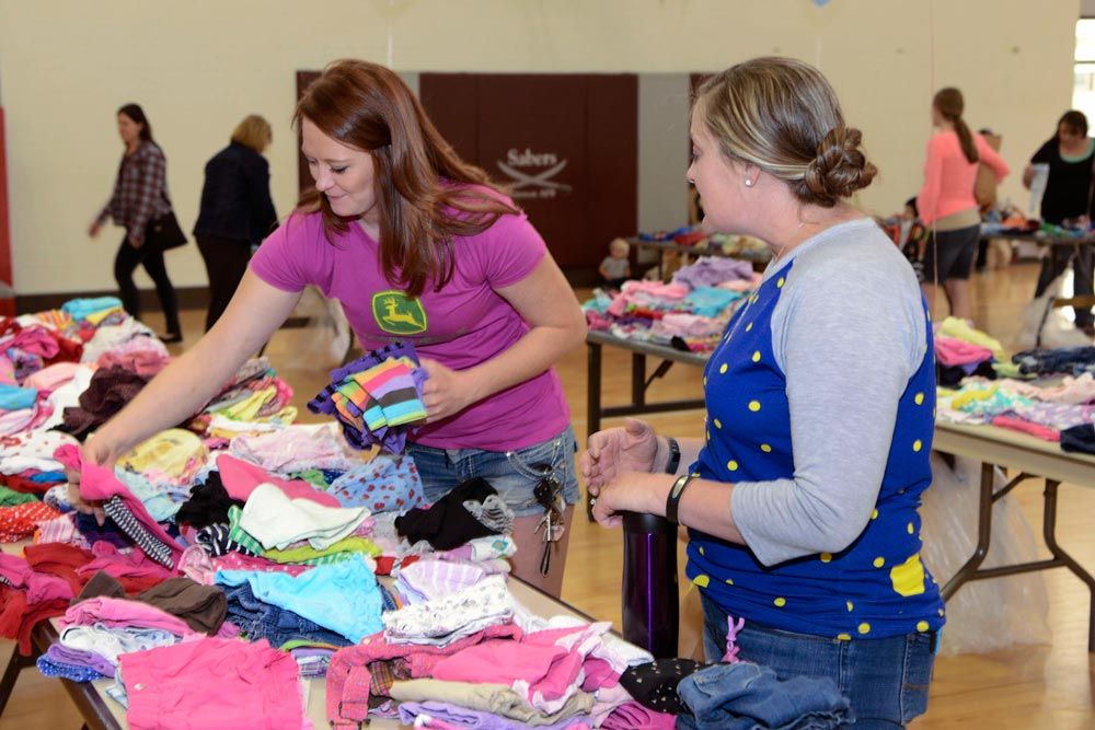 PETERSON AIR FORCE BASE, Colo. — Stephanie Thien, (right), wife of Lt. Col. John Thein, 25th Space Range Squadron commander at Schriever Air Force Base, Colo. talks with shopper Andrea Mitchell during the annual clothing swap at the Peterson Youth Center April 23, 2016. Thien was the primary organizer of this year's event.
