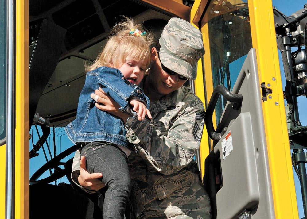 (U.S. Air Force photo by Airman 1st Class Rose Gudex) PETERSON AIR FORCE BASE, Colo. — Chief Master Sgt. Idalia Peele, outgoing 21st Space Wing command chief, helps a child down after showing her the inside of a snow plow during the 21st Civil Engineer Squadron Snow Parade on Peterson Air Force Base, Colo., Oct. 28, 2014. One of Peele's greatest priorities as the command chief was interacting with Airmen and their families. She retired from the Air Force Sept. 1, 2016 after more than 29 years of service.