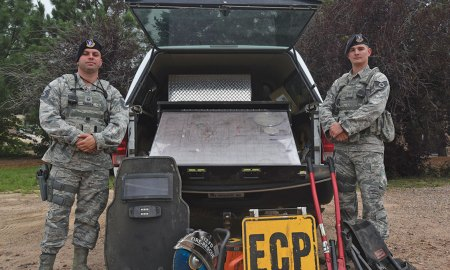 U.S. Air Force photo/Airman 1st Class William Tracy Master Sgt. Brady Warren, 50th Security Forces Squadron flight sergeant, and Staff Sgt. Chance Dobbins, 50 SFS Base Defense Operations Center controller, stand next to equipment used during emergency situations at Schriever Air Force Base, Colorado, Monday, Aug. 7, 2017. August is Anti-terrorist Awareness Month, which is dedicated to spreading awareness and information on anti-terrorist measures for base and individual safety.