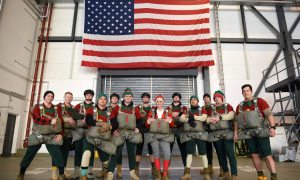 RAMSTEIN AIR BASE, Germany (AFNS) — Mrs. Claus poses with 12 of Santa's elves for a photo after being rigged into their parachutes for Operation Toy Drop 2018 at Ramstein Air Base, Germany, Dec. 13, 2018. Members of the 5th Quartermaster Theater Aerial Delivery Company worked with the 435th Air Ground Operations Wing, 86th Airlift Wing, and seven coalition partners. (U.S. Air Force photo by Airman 1st Class Kristof J. Rixmann)