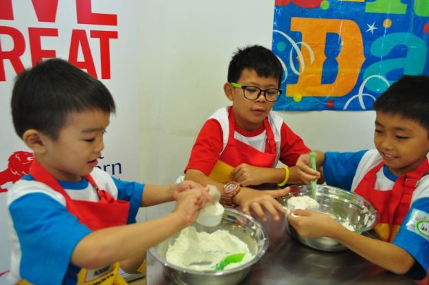 A group of children learning the basics of baking at the start of the class.