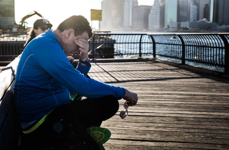 man putting his head in his hands, looking frustrated, sitting on a pier