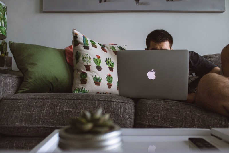 man on a couch with a computer