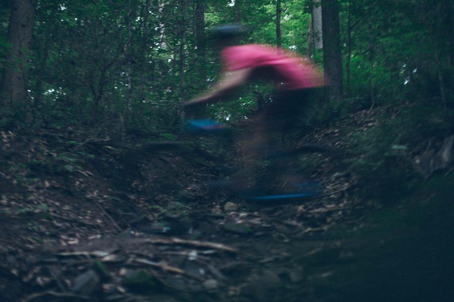 A blurry man wearing a red shirt on a blue bike speeding through the forest.
