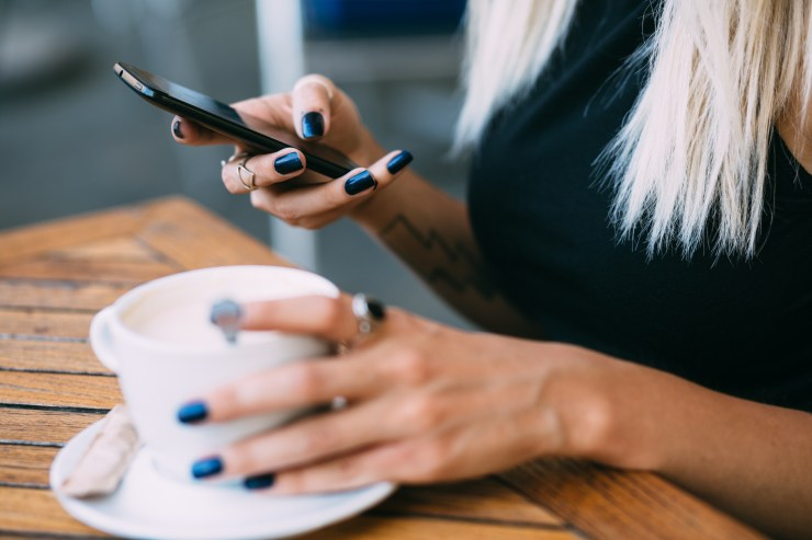 Young, retro woman drinking coffee and using a smart phone