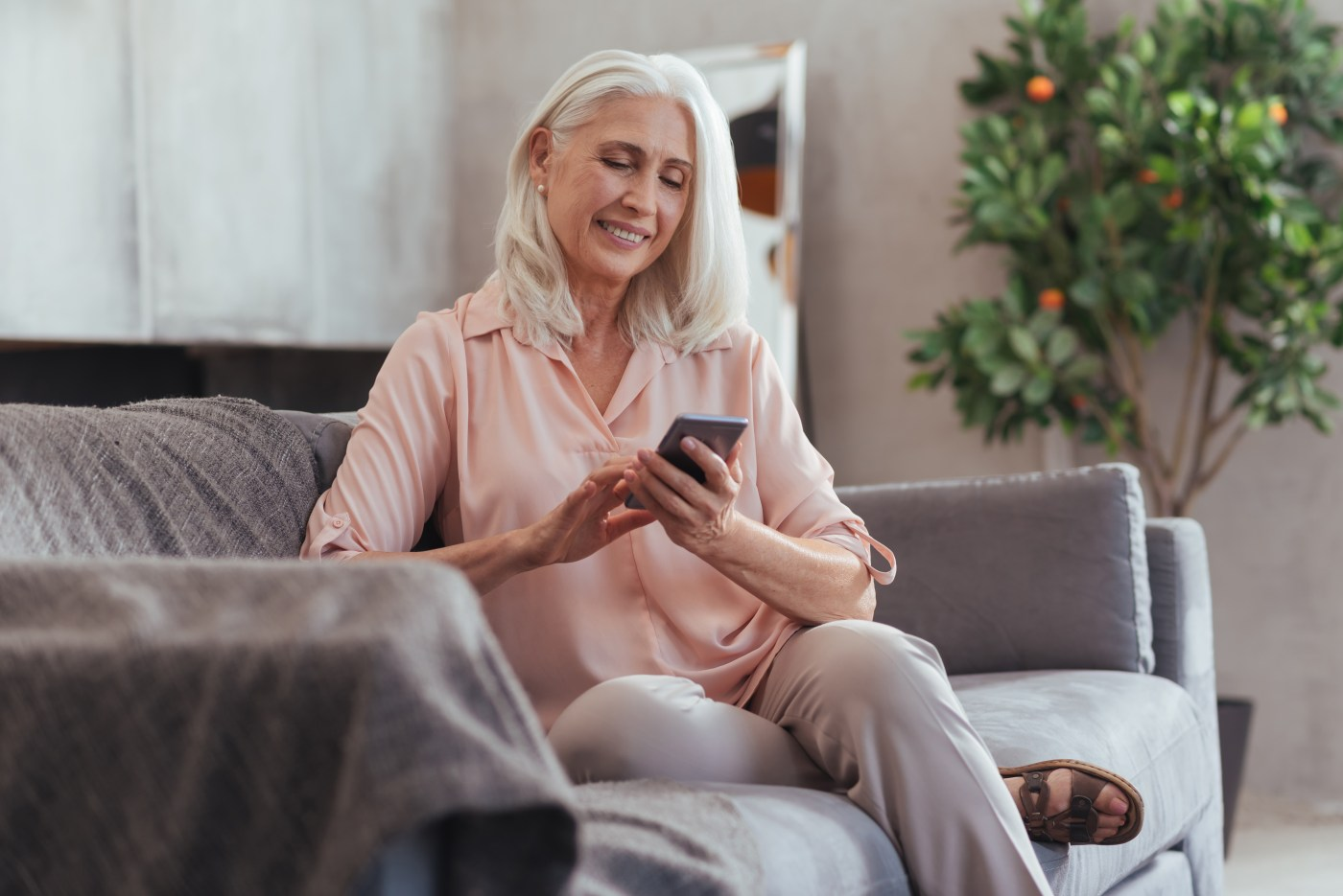 Mature woman sitting on couch using a smart phone