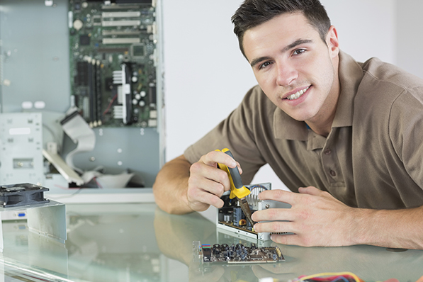 Handsome smiling computer engineer repairing hardware with pliers in bright office