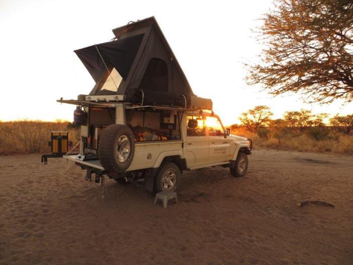 Jeep met daktent bij ondergaande zon op camping Deception in de Kalahari
