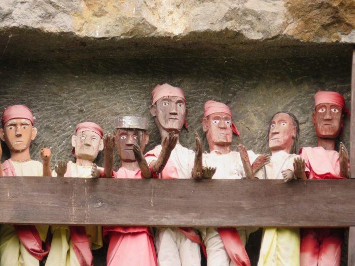 7 houten Tau Tau poppen in rotswand
