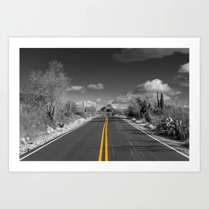 Art print of road across a black and white desert with the yellow lines leading the eye to the distance