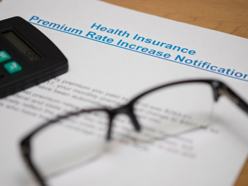 Image of a notice of increasing in premium rate of health insurance with a pair of glasses and a calculator. (Doubletree Studio via Shutterstock)