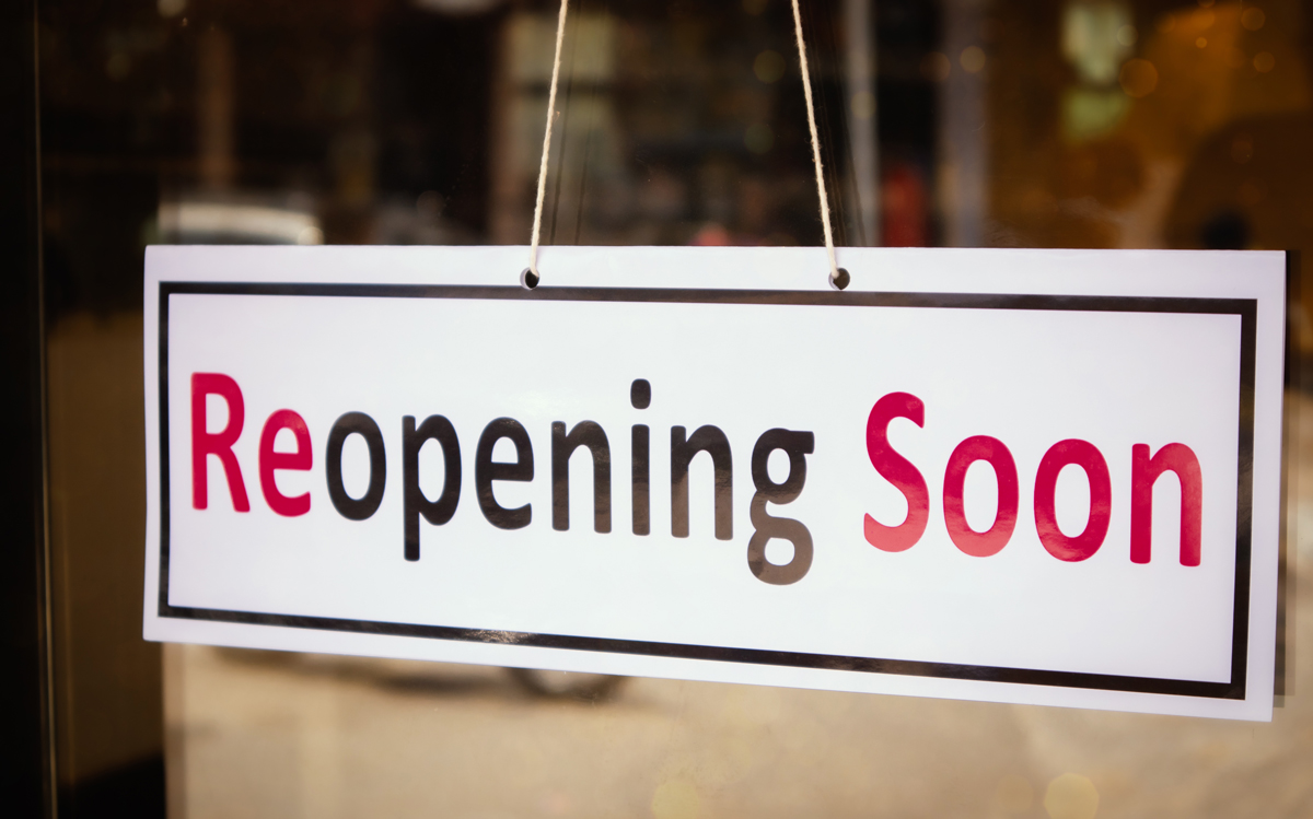 Image of a reopening soon sign on a business door after COVID-19 outbreak - Concept of back to business after pandemic. (Lakshmiprasada via Shutterstock)
