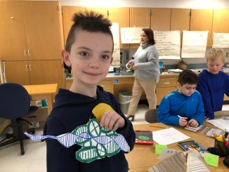 A 3rd grade student at Lanesborough Elementary School displays his graphic visualization of DNA sequencing, part of a computational thinking, pattern-recognition exercise.