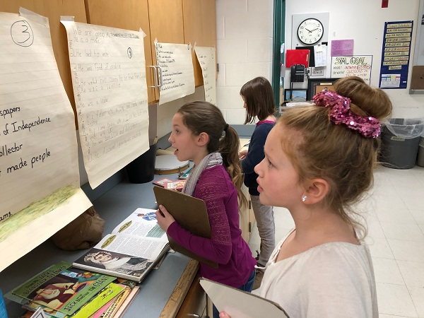 Third graders at the Lanesborough Elementary School study clues taped to their classroom wall about ten Revolutionary War heroes in a lesson on computational thinking.