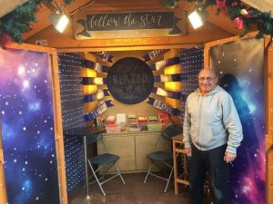 man standing by Christmas chalet