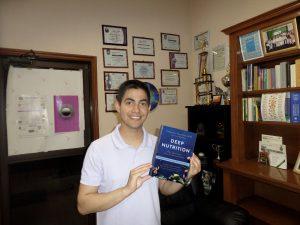 El Lic. Ramsés Rodríguez con el libro de Deep Nutrition.
