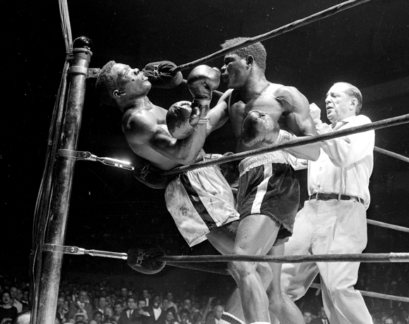 UNITED STATES - MARCH 24: Emile Griffith vs Benny Paret, Benny (Kid) Paret lies helpless against ropes as flailing fists of Emile Gfriffith batter him into unconsciousness during twelfth round of their welterweight championship fight at the Garden . Ref Ruby Goldstein pulled Griffith off the champ who slumped to the canvas. It was ruled a TKO at 2:09 of the twelfth. paret was removed, still unconscous, to Roosevelt Hospital after getting last rites in dressing room. (Photo by Charles Hoff/NY Daily News Archive via Getty Images)