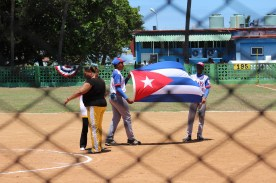Team Playa players present the Cuban flag during the pre-game national anthem.