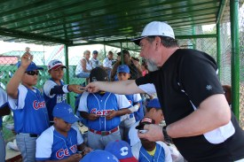 Jim Court of the Cuban American Friendship Society, hands out baseball cards prior to the game with Cerro.