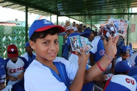 A Cerro player holds up a handful of new baseball cards given to him by the Vermonters.